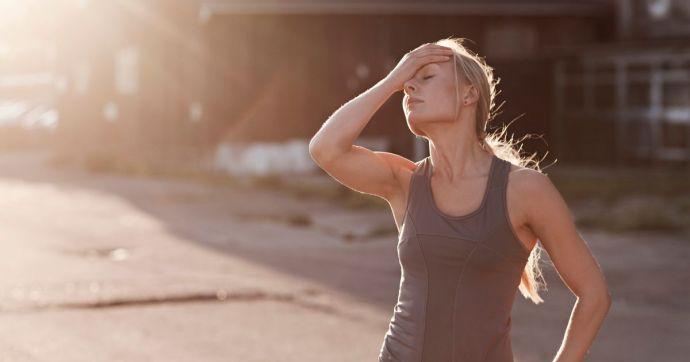 Female-runner-resting-on-suburban-street