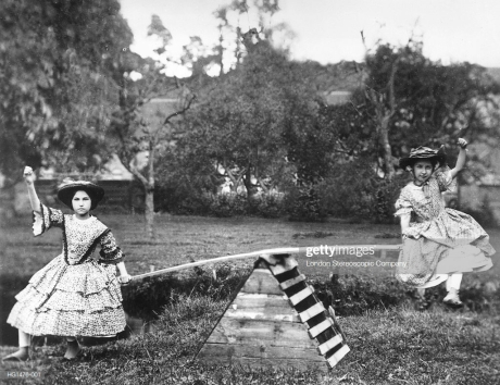Two young girls in long layered dresses and hats riding on a see-saw.